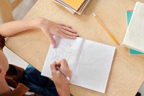 Clean classroom and student taking notes in notebook