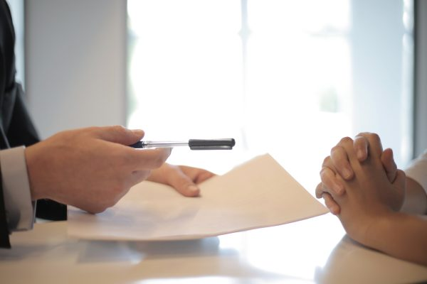Hands Holding Pen and Insurance Papers